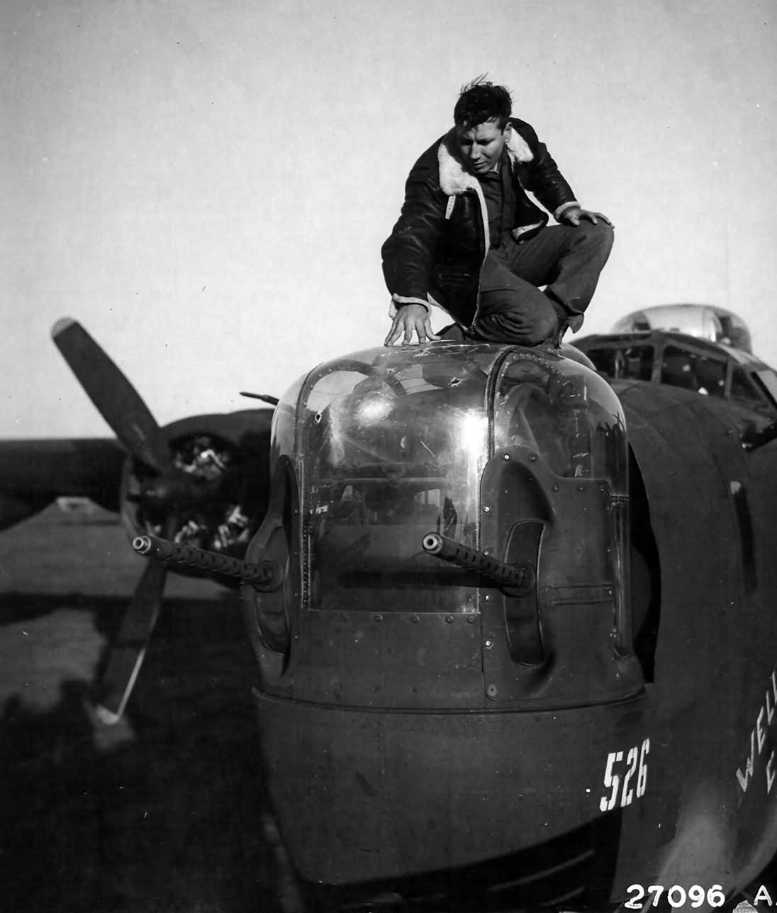 B-24_Liberator_Wells_Cargo_Navigator_2nd_Lt._Joseph__Orley_examines_the_holes_in_his_nose_turr...jpg